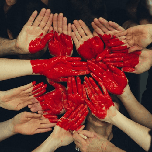 hands together face up with red paint in the shape of a heart