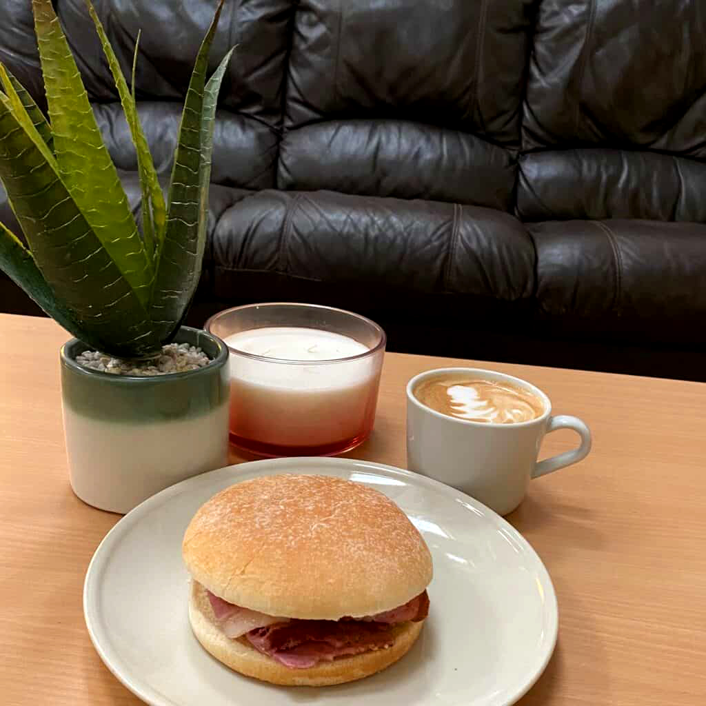 bacon bap with coffee on a table