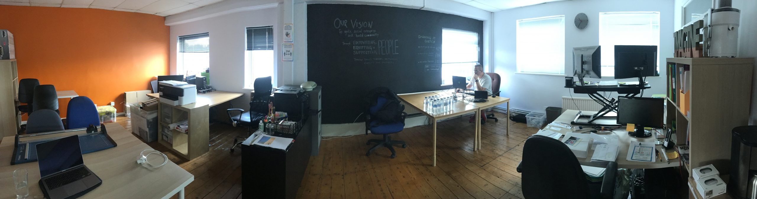 panoramic view of coworking offices with desks and equipment